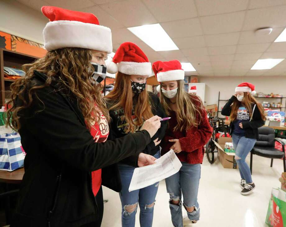 Misty Westover, left, goes over plans with her daughter, Olivia, and Madie Moore as volunteers and members of Communities in Schools distribute Christmas gifts to students in middle and high school at Conroe High School, Thursday, Dec. 17, 2020, in Conroe. Photo: Jason Fochtman, Houston Chronicle / Staff Photographer / 2020 © Houston Chronicle