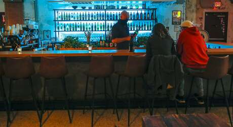 Owner Mike Sammons chats with customers Nena Higginbotham and Louis Warner at the bar of How to Survive on Land & Sea Wednesday, December 16, 2020, in Houston. Sammons, formerly of 13 Celsius, Midtown cocktail bar Mongoose versus Cobra, and Weights + Measures, has opened this wine bar in a deco building at 3401 Harrisburg, in November of 2019. He hosts Giant Leap Coffee, and Tlahuac and Papalo pop ups, while those businesses wait to move into their new spaces.