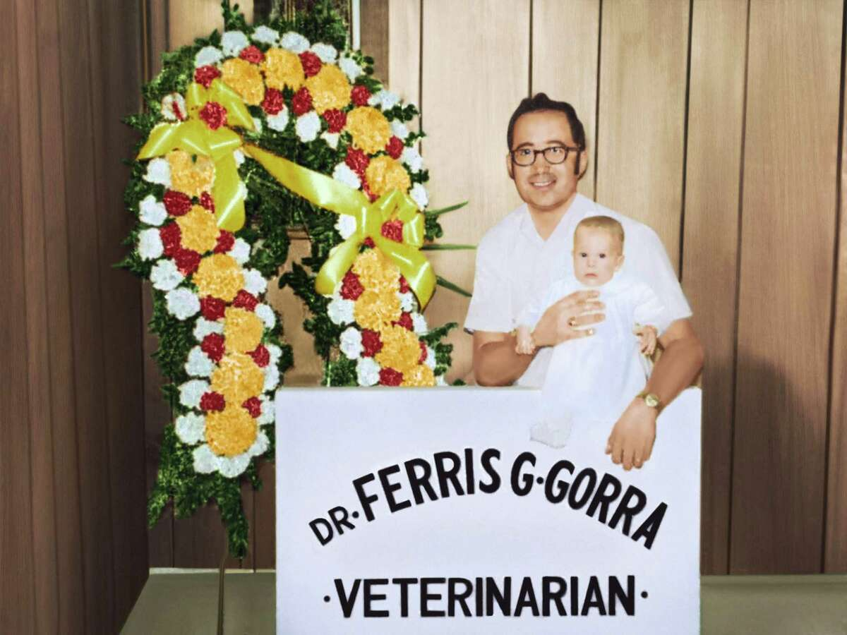 Ferris Gorra, who founded Aspetuck Animal Hospital 50 years ago, is shown holding his son, Michael, 3 months, in 1970. Michael now owns the business with fellow vet Trish Grinnell.