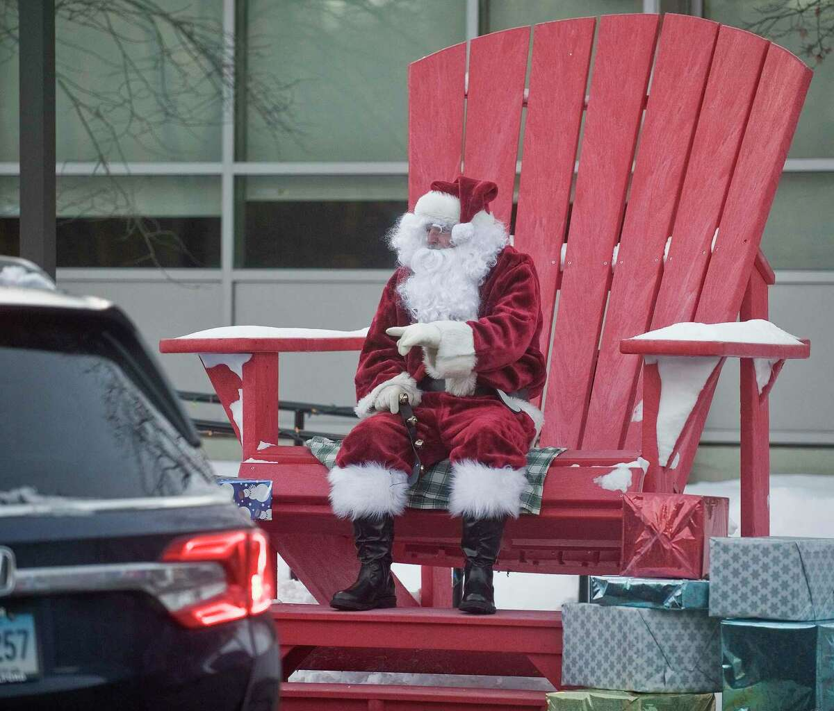 Santa Claus (Steve Pierce), chats with families in cars as they drive through Comstock Community Center.