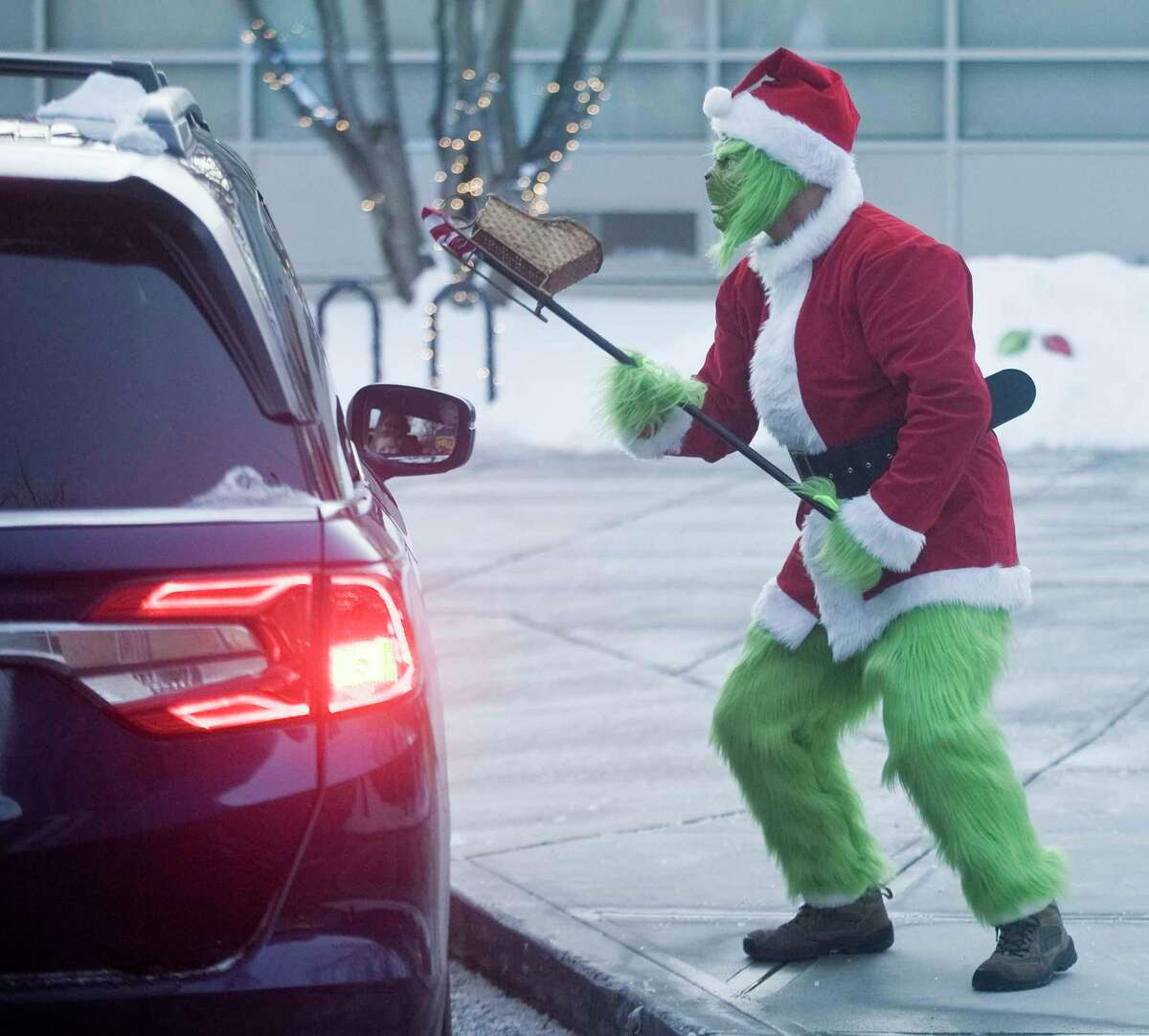 Right, Jim Lewicki, dressed as the Grinch, waits for cars to pull up so he can pass candy through the window.