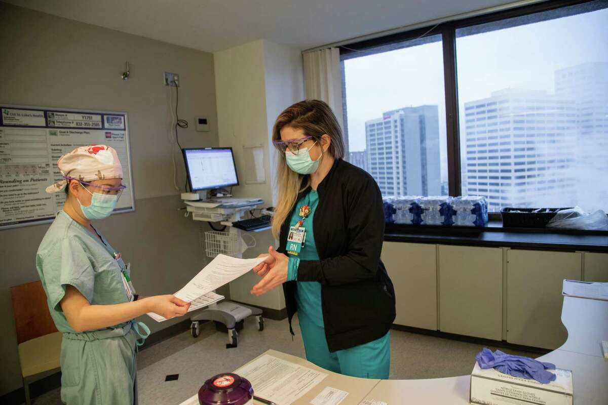 Baylor St. Luke's Medical Center registered nurse Linda Fletcher receives paperwork from register nurse Mary Ju before Ju gets inoculated with Pfizer's COVID-19 vaccine, Tuesday, Dec. 15, 2020, in Houston. Ju was the first person the hospital vaccinated and Fletcher was the first to vaccinate a member of the staff.