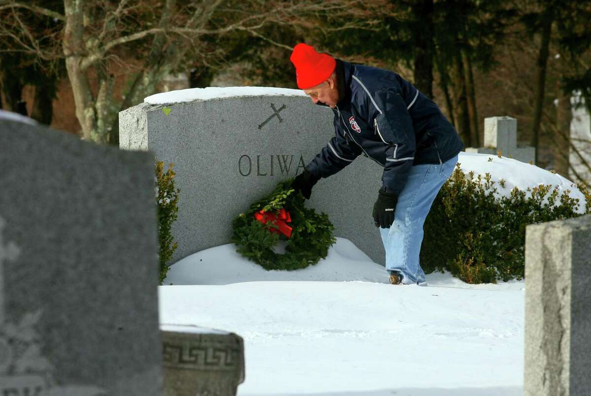 Gene Sharkey, Chairman with the Ansonia Fire Commission, places a wreath in front of a veteran's grave during a Wreaths Across America event held at St. Michael's Cemetery in Ansonia, Conn., on Saturday Dec. 19, 2020. Residents and dignitaries laid some 400 wreaths on the graves of veterans at St. Michael's Cemetery during the Valley's first ever Wreaths Across America event.