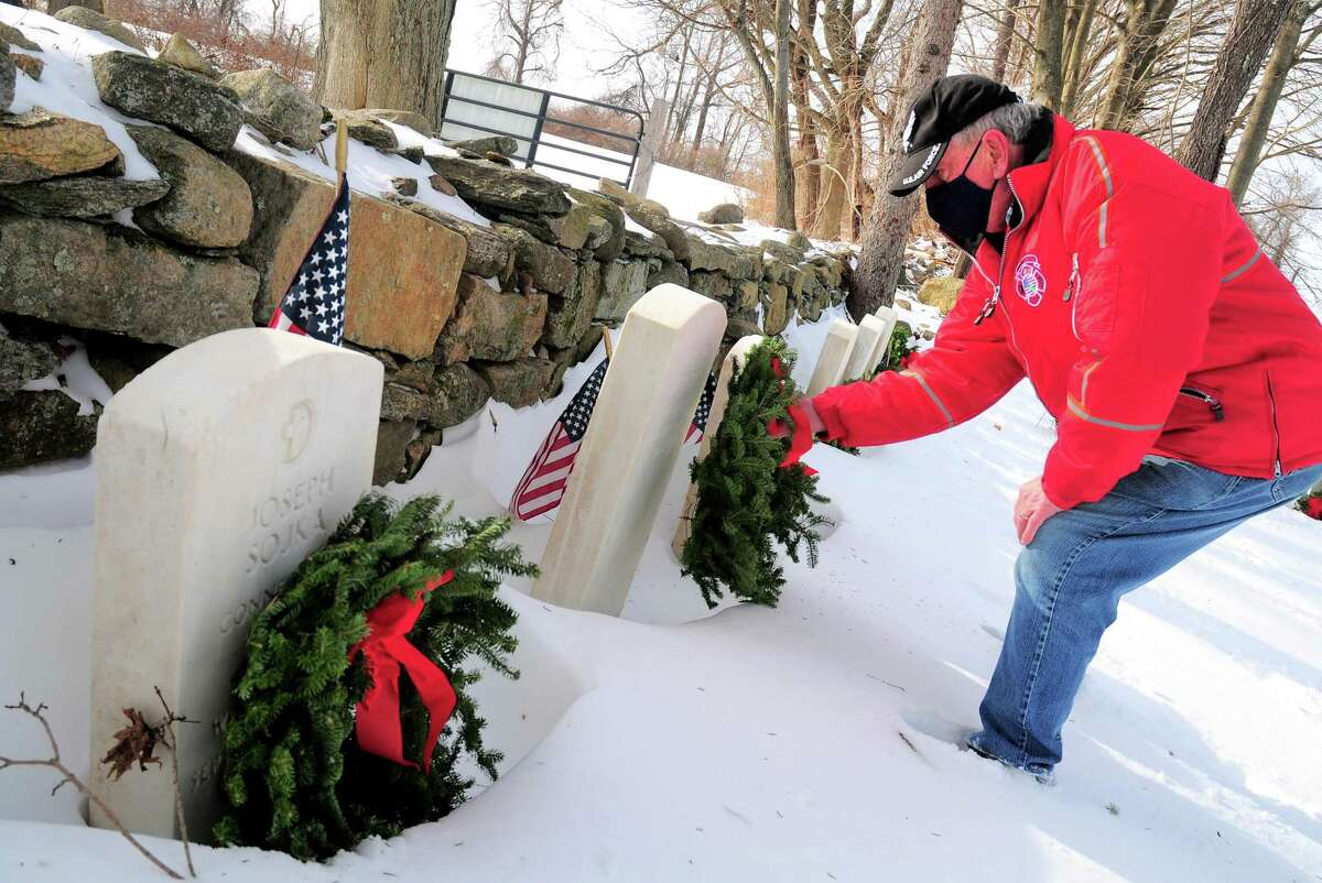 Firefighter Rich Barrows places a wreath in front of a veteran's grave during a Wreaths Across America event held at St. Michael's Cemetery in Ansonia, Conn., on Saturday Dec. 19, 2020. The Valley's participation in Wreaths Across America was arranged by Pauline Totaro, president of the Catholic War Veterans Post 1562 Auxiliary. Her son, Jason, a U.S. Army veteran, participates in the annual Wreaths Across America ceremony at the Arlington National Cemetery, she said.