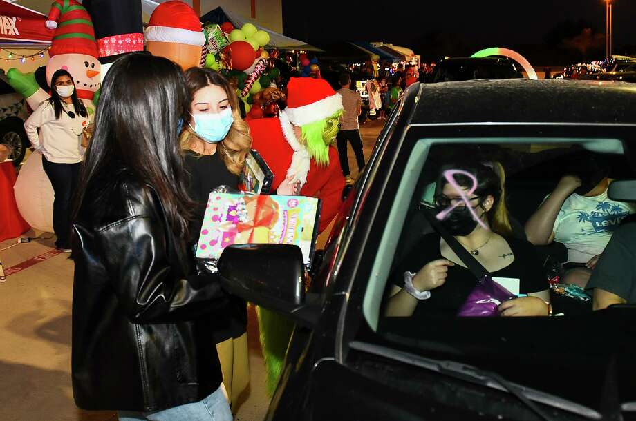 Volunteers help distribute gifts from the Smiles from Heaven booth, Saturday, Dec. 19, at Pla-Mor during the Smiles from Heaven Drive-Thru Toy Giveaway. Photo: Danny Zaragoza, Staff Photographer / Laredo Morning Times