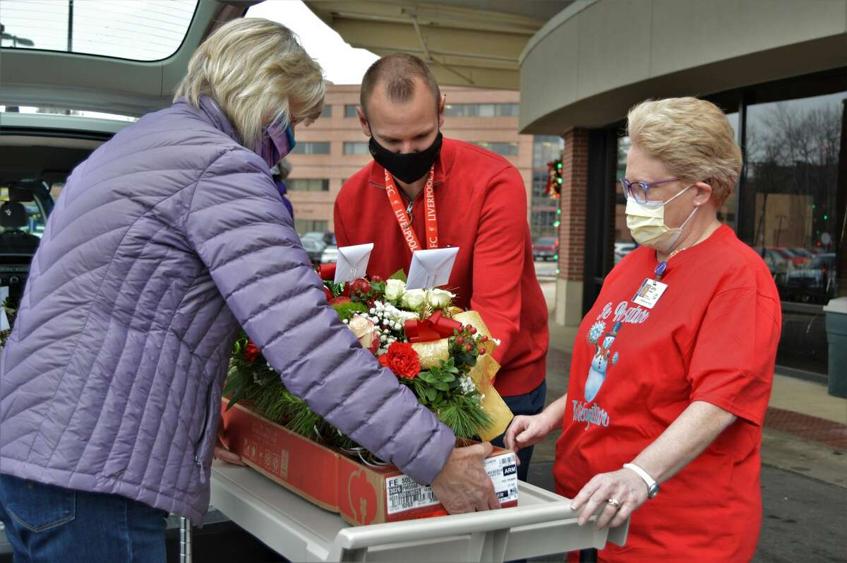 Volunteers from the Women of Michigan Action Network (WOMAN) stopped by the Midland hospital Monday morning, Dec. 21, 2020, to drop off donated gifts to more than a dozen nursing units. Nurses from each unit met the WOMAN members in the lobby at MidMichigan Health Medical Center - Midland to accept gift bags with snacks, treats and donated flower arrangements. (Ashley Schafer/ashley.schafer@hearstnp.com)