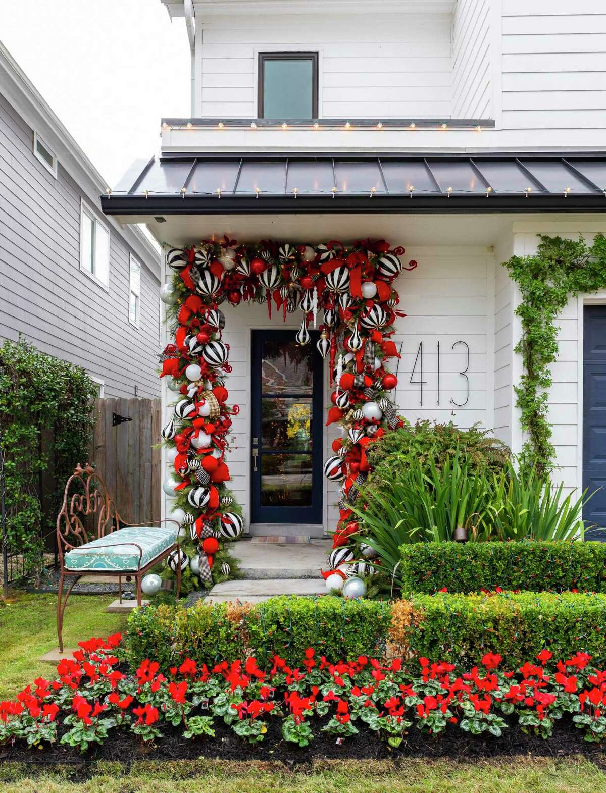 More than 300 bulbs in red or black and white hang on garland around the front door. Red cyclamen in the yard offer complementary holiday color.