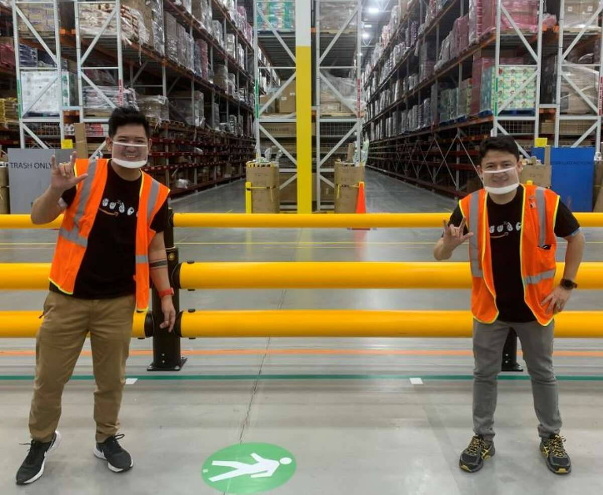 Ronnie Lim and Cristiano de Castro Assumpcao Koyama (l-R) are both deaf and they are teaching sign language at Schodack's Amazon facility. There are a half-dozen deaf employees. Lim is from the Philippines and Koyama is from Brazil.