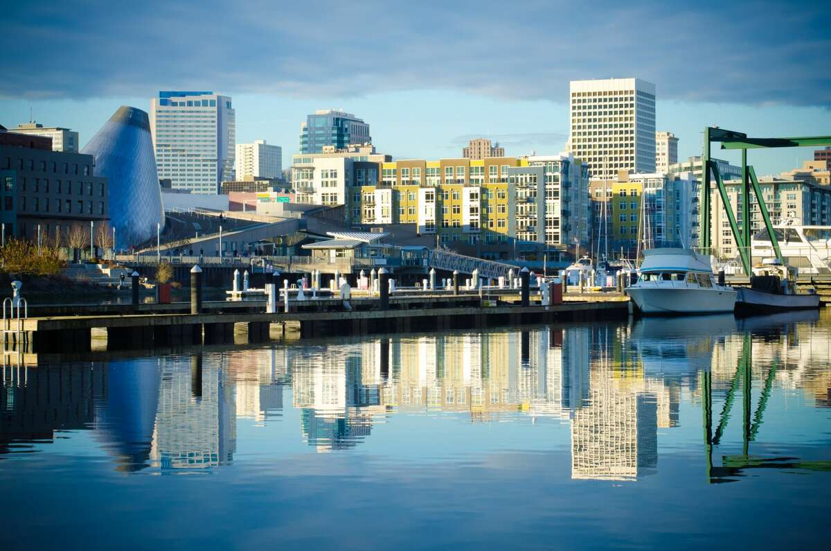 Skyline consisting of office buildings, condominiums and museums of Tacoma, WA reflects off of the Foss Waterway.