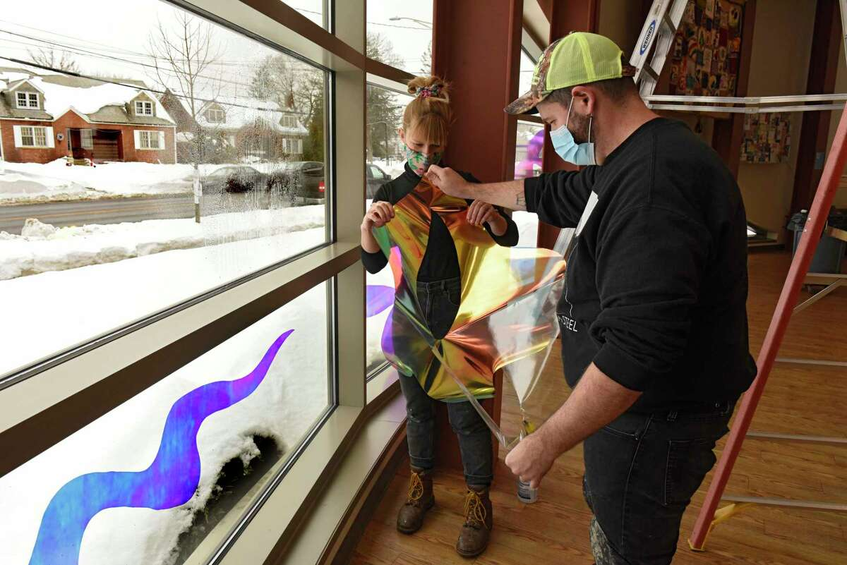 """Troy artists Gracelee Lawrence, left, and Benjamin Seretan work on a new public art exhibition ?'A Beneficent Fluid Bathes Us,?"""" on the front windows of the Bach Branch of Albany Public Library on Monday, Dec. 21, 2020 in Albany, N.Y. The installation is part of the Creative Curbsides project in partnership with Opalka Gallery. (Lori Van Buren/Times Union)"""