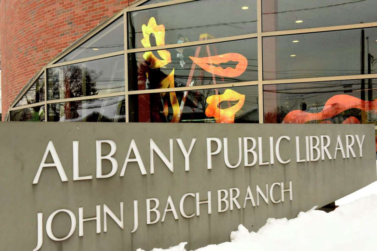 """Troy artists Benjamin Seretan and Gracelee Lawrence work on a new public art exhibition ?'A Beneficent Fluid Bathes Us,?"""" on the front windows of the Bach Branch of Albany Public Library on Monday, Dec. 21, 2020 in Albany, N.Y. The installation is part of the Creative Curbsides project in partnership with Opalka Gallery. (Lori Van Buren/Times Union)"""