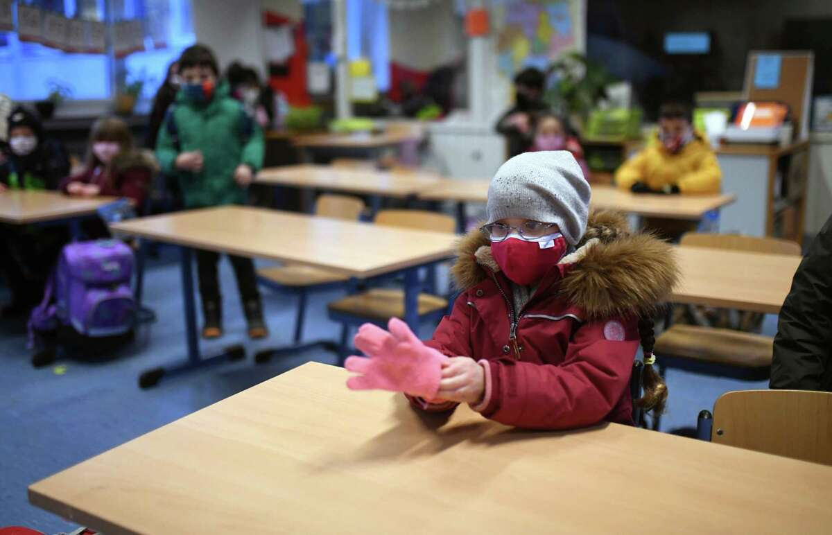 A girl takes off her gloves in her classroom with the window open at the Petri primary school in Dortmund, western Germany, on Nov. 24, amid the COVID-19 pandemic.