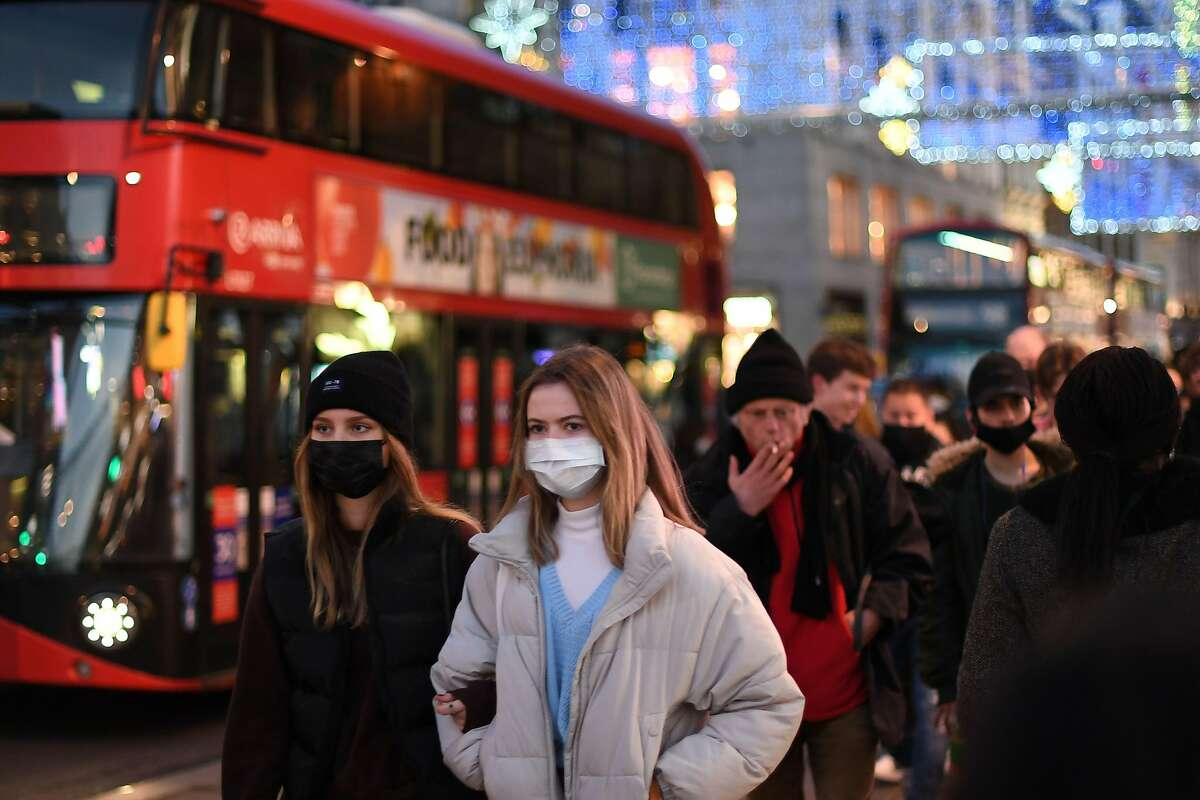 Shoppers, some wearing masks because of the coronavirus pandemic, walk along Regent Street in a London shopping area.