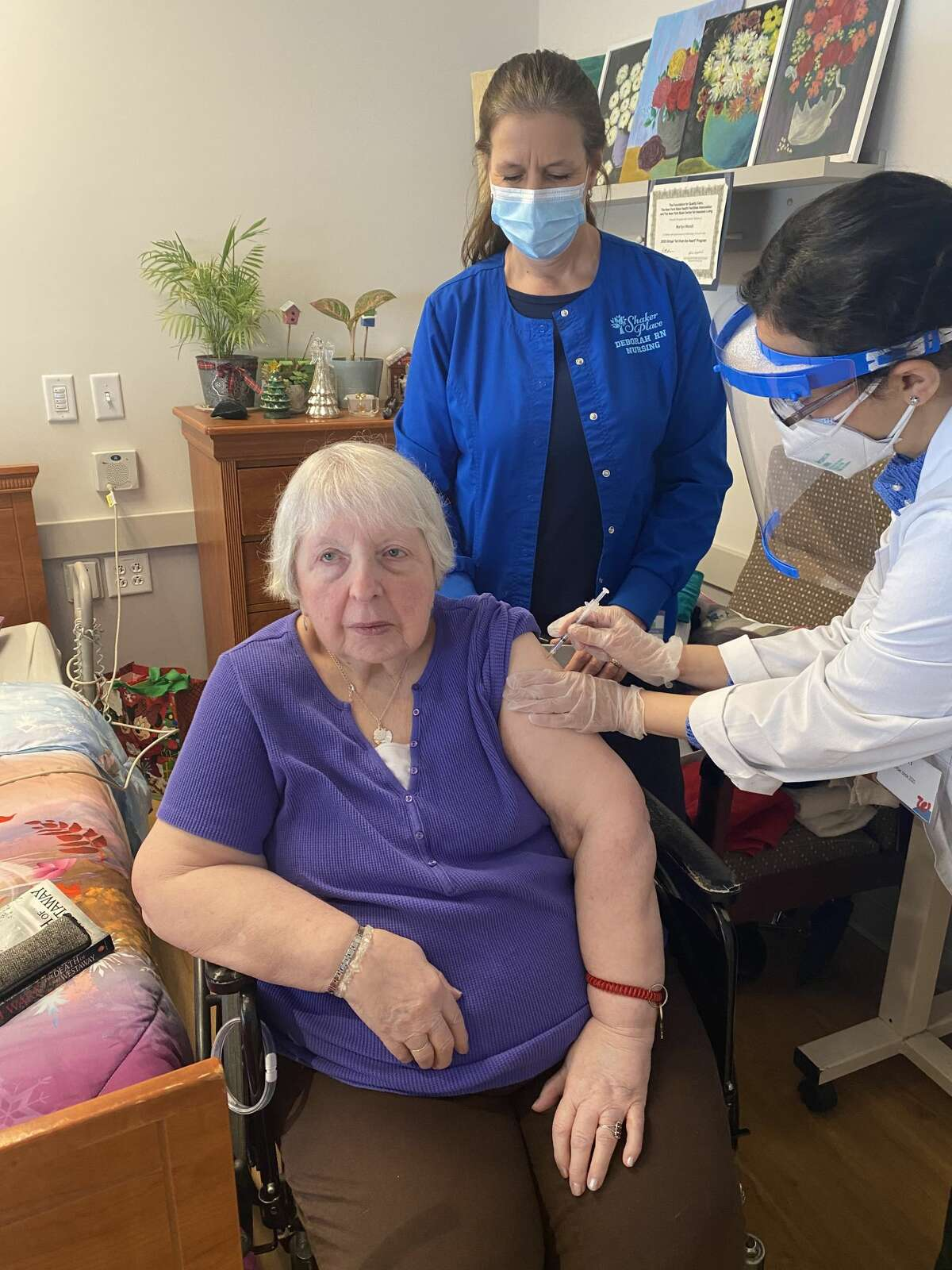 Walgreens staff administer the first COVID-19 vaccine to a resident of the Albany County-run Shaker Place nursing home in Colonie, N.Y. on Monday, Dec. 21, 2020. County officials declined to release the resident's name, citing privacy concerns.
