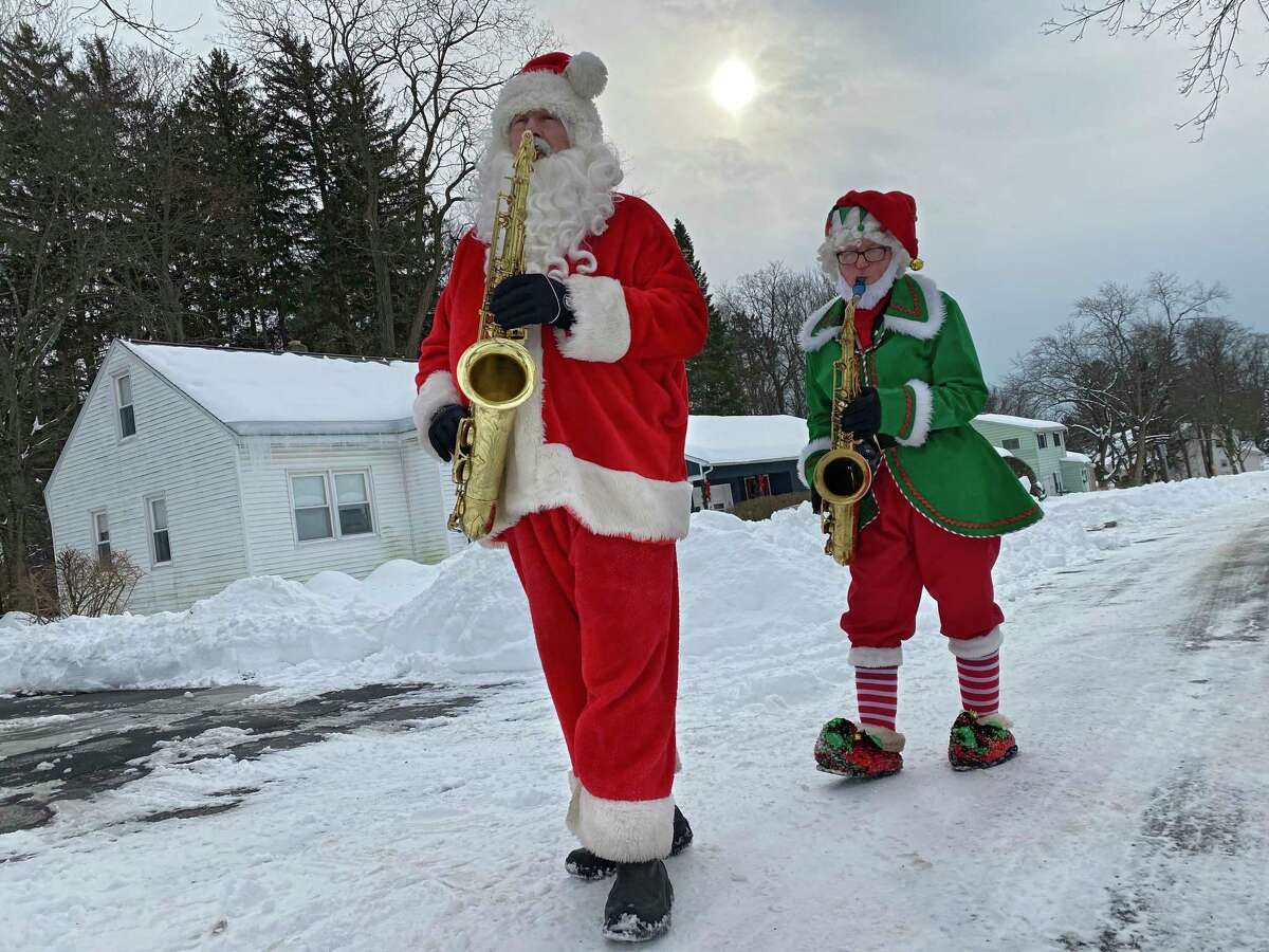 Luke McNamee as Sax-O-Clause and his elf Josh Greenberg play Christmas tunes on their saxophones to neighbors as they walk a few streets on Sunday, Dec. 20, 2020 in McKownville, N.Y. (Lori Van Buren/Times Union)