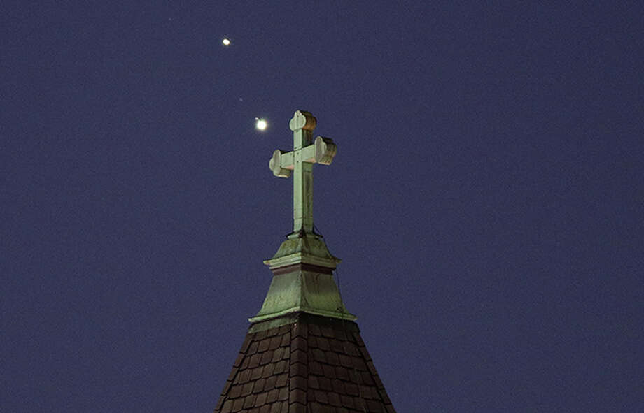 Saturn and Jupiter appear behind a church ahead of their conjunction tonight. The two will appear as one big bright spot, which many are calling the Christmas Star. Photo: Gary Hershorn | Getty Images  / 2020 Gary Hershorn