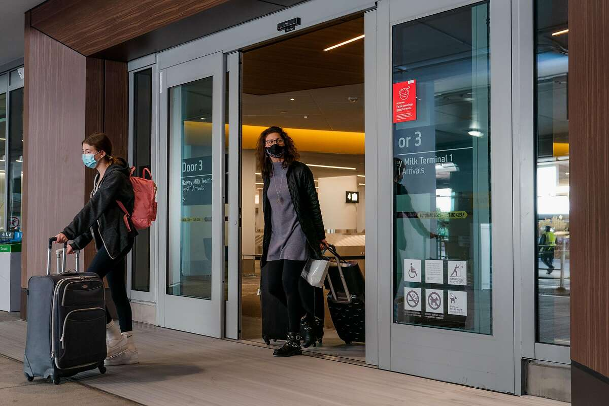 Travelers exit Terminal 1 at San Francisco International Airport on Friday, December 18, 2020.