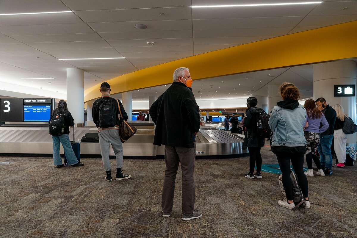A group of travelers wait for their luggage to arrive at San Francisco International Airport on Friday, December 18, 2020.