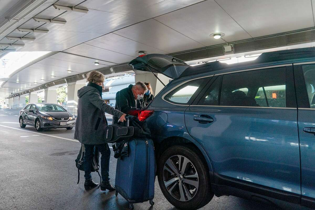 A group of travelers loads their baggage into the back of a vehicle after arriving at San Francisco International Airport on Friday, December 18, 2020.