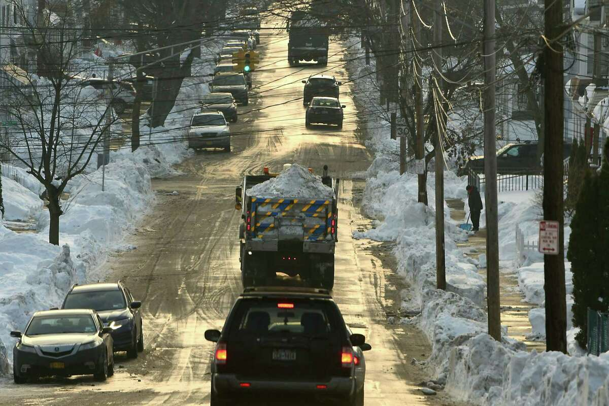 Dump trucks full of snow are seen on heading down a street on Monday, Dec. 21, 2020 in Schenectady, N.Y. Snow is still being removed from streets and dumped in a parking lot near Central Park. (Lori Van Buren/Times Union)