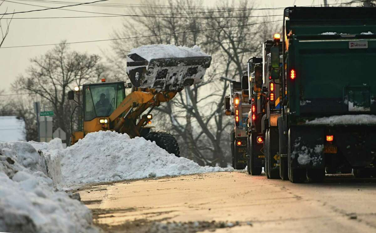 A front loader is seen dumping snow into trucks lined up on a street on Monday, Dec. 21, 2020 in Schenectady, N.Y. Snow is still being removed from streets and dumped in a parking lot near Central Park. (Lori Van Buren/Times Union)