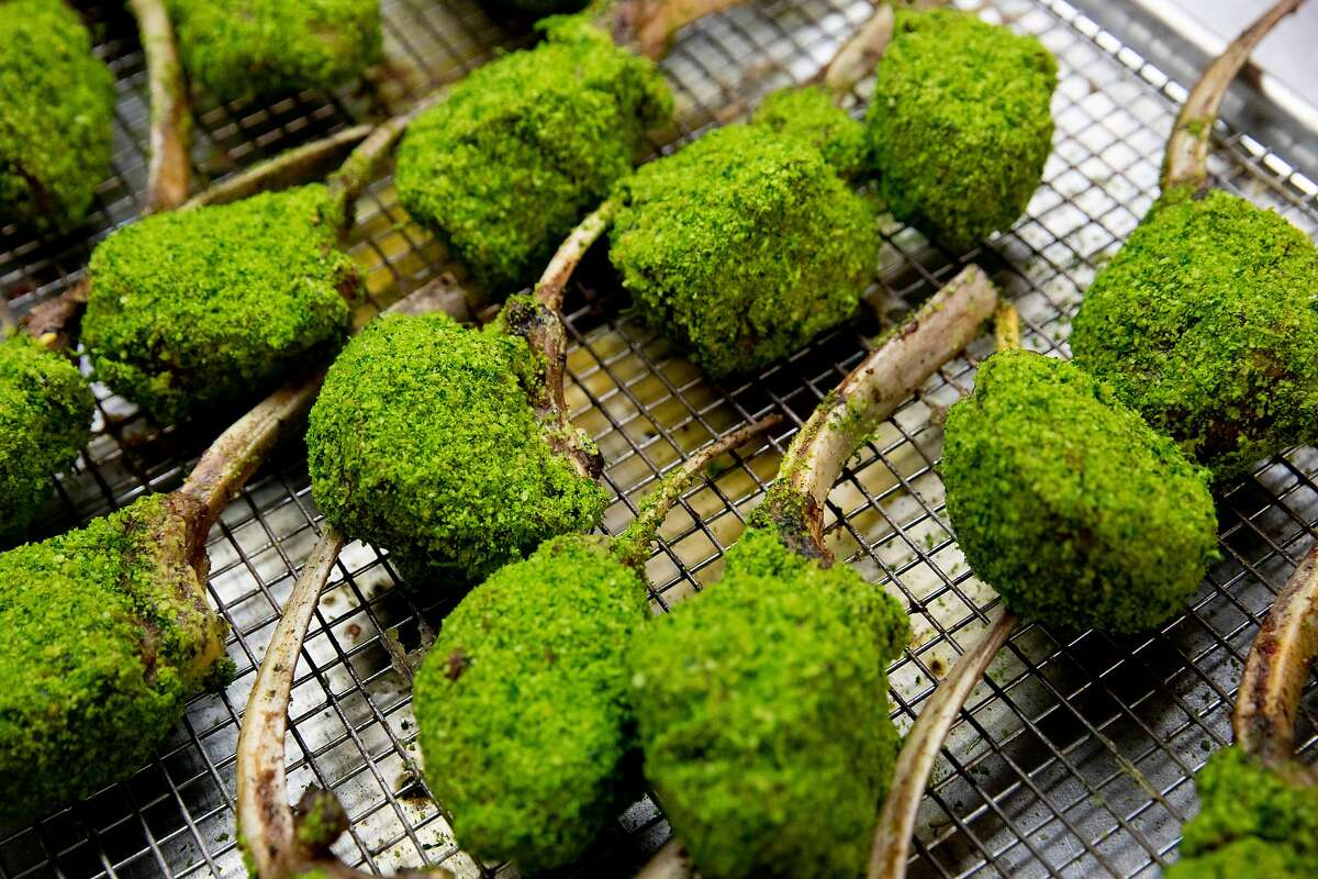 Herb-crusted racks of lamb wait to be packaged as part of food boxes for virtual galas.