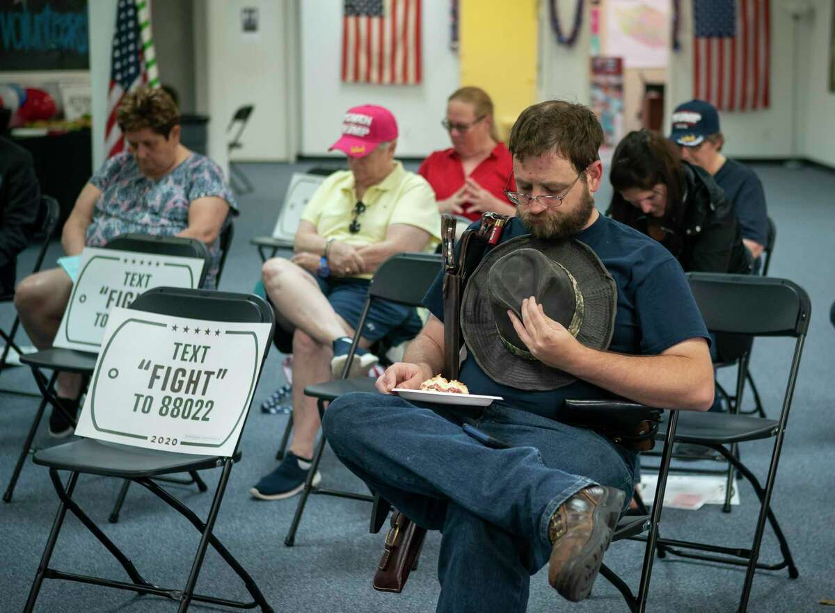 Kenny Wolfam prays at the beginning of an event for veterans and second amendment supporters at the Trump campaign office in Katy, TX, Friday, Sept. 25, 2020.