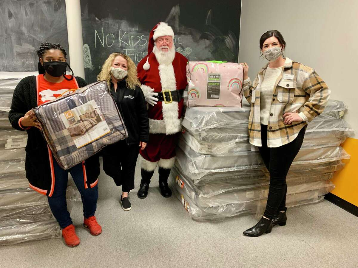This year, the Houston Furniture Bank received 250 Bed-In-A-Bag sets from Ashley HomeStore to give to children in need along with a new bed. The sets will be distributed from the furniture bank's location in The Woodlands. Santa and some of his elves unpack the donated sets at the Houston Furniture Bank location in The Woodlands on Dec. 21, 2020.