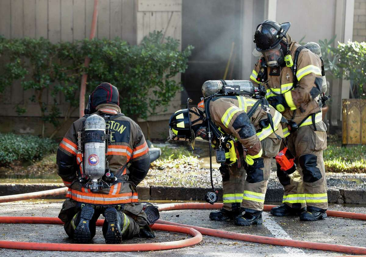 Houston Fire Department firefighters at a two-alarm fire at The Bellfort Apartments complex Thursday, Nov. 19, 2020, in Houston.