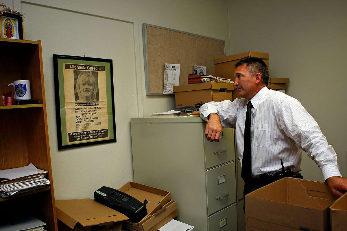 """Then-Hayward police Sgt. Eric Krimm showing """"Michaela's room"""" at the Hayward police station in 2012. He is looking at a framed ad searching for any information on Michaela Garecht, who was abducted Nov. 19, 1988."""