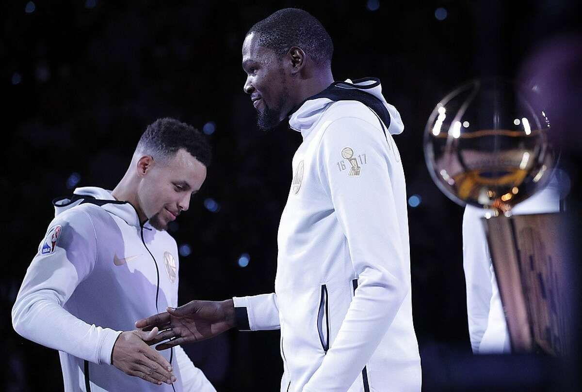 Stephen Curry (30) shakes Kevin Durant's (35) hand as he goes up to get his ring before the Golden State Warriors played the Houston Rockets at Oracle Arena in Oakland, Calif., Tuesday, October 17, 2017.