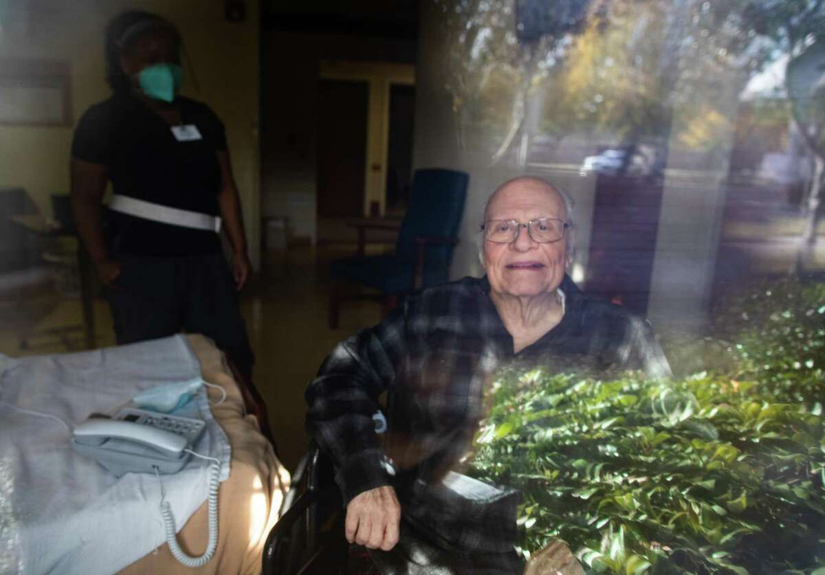 Ollie Moffitt, 86, looks out a window from his nursing home room, Monday, Dec. 21, 2020, in Houston. His wife visits him four to five times a week.