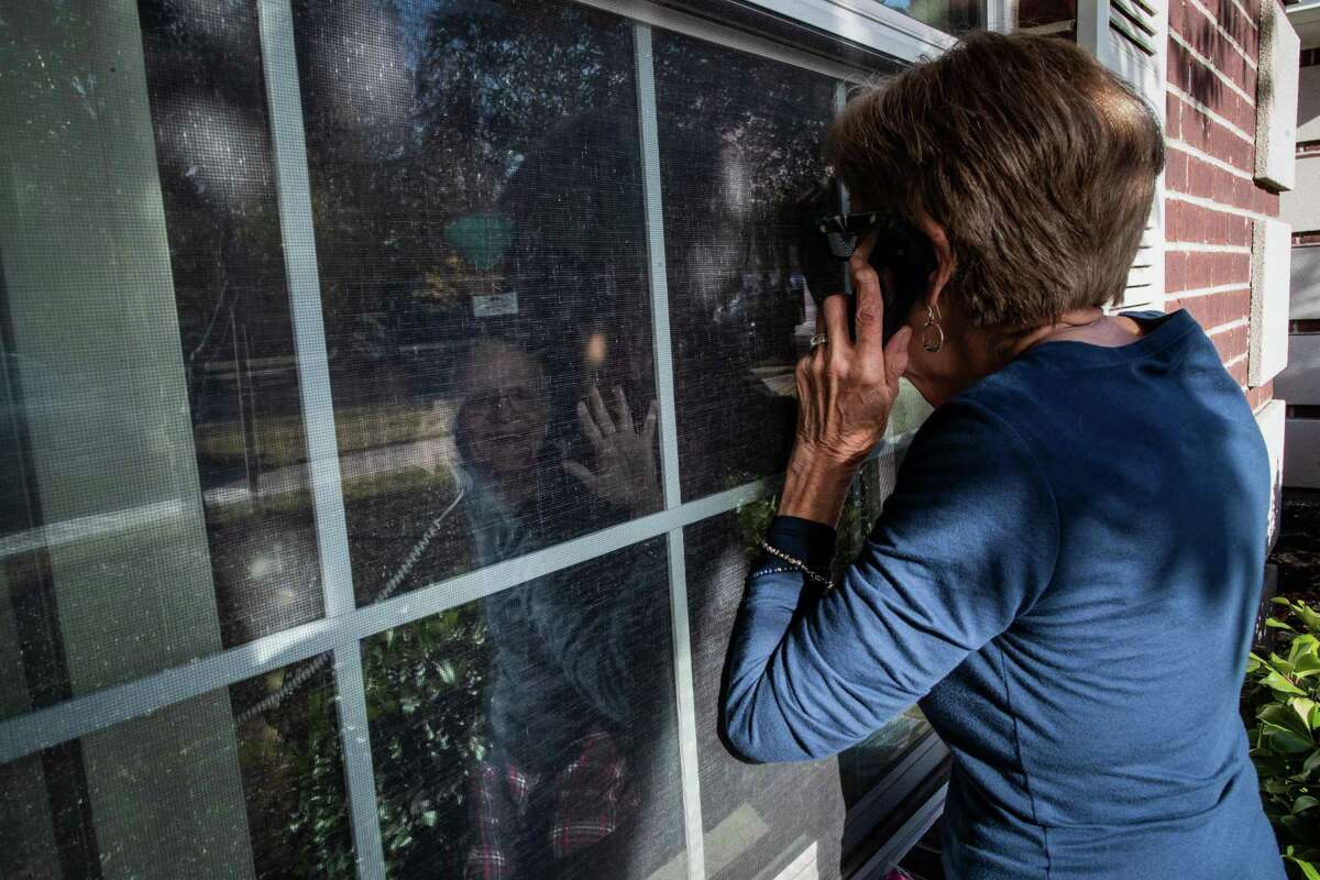 Ollie Moffitt, 86, waves as his wife Connie Moffitt arrives to the window of his room at Park Manor of Westchase to visit him, Monday, Dec. 21, 2020, in Houston. Connie visits him through the window four to five times a week.