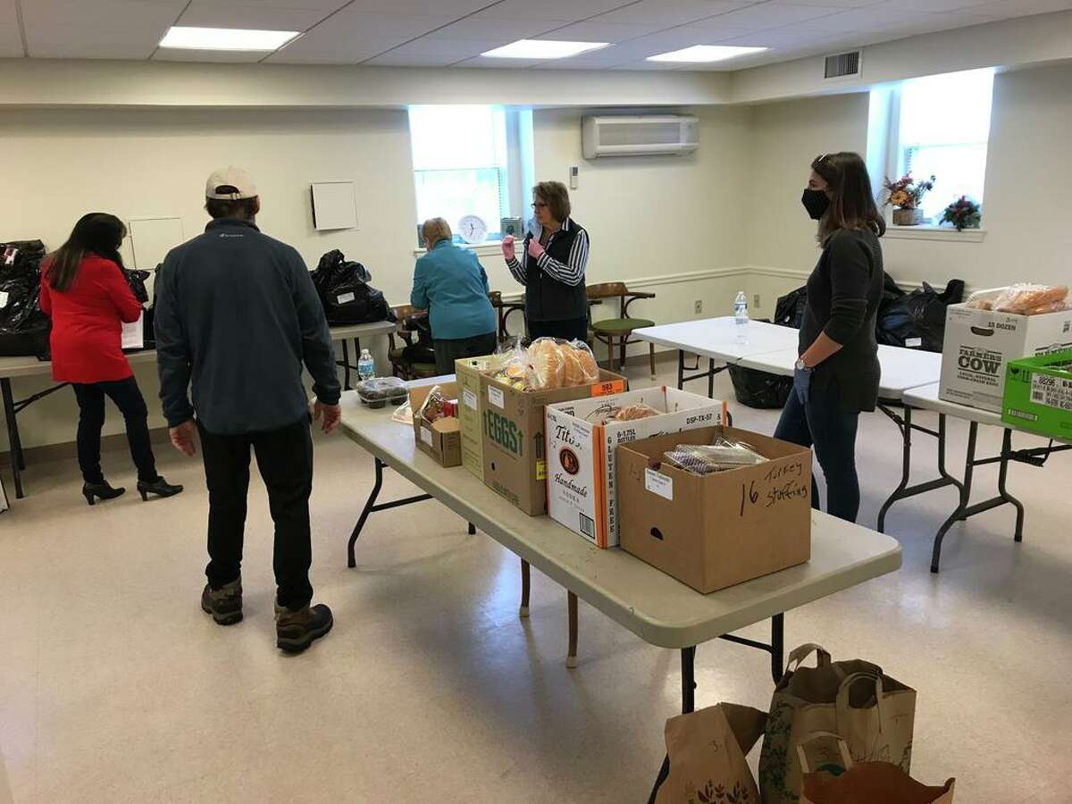 Monday was Distribution Day for 101 residents who received food, gift cards and toys from the Portland Food Bank. Here, volunteers organize the items.