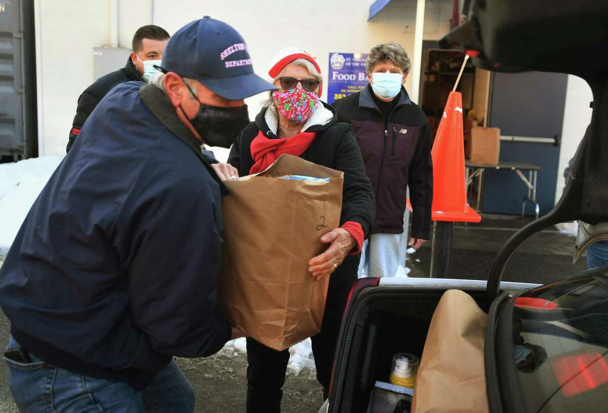 Above, volunteers Ken Baldyga, of Shelton, and Jean Whalen Smuckler, of Southbury, load holiday groceries into the trunks of a long line of cars during the annual Christmas food and gift distribution at the St. Vincent de Paul Food Bank in Derby on Monday. At left,