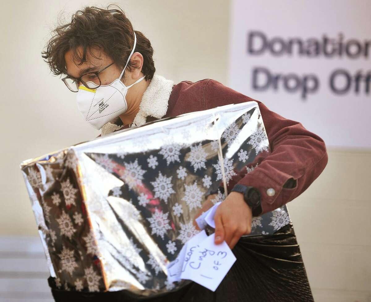 Sam Kocurek, of Shelton, carries a bag of gifts.