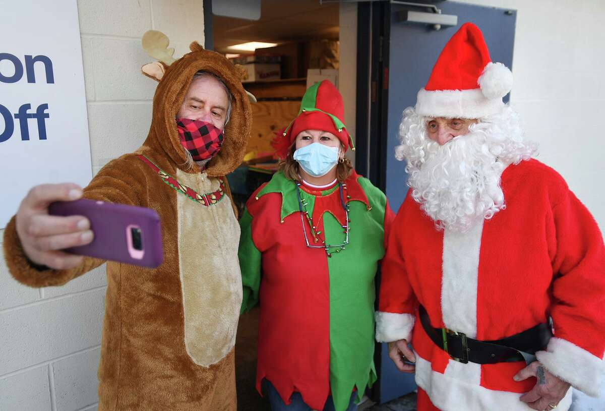 From left; Volunteers Will Lasse, Cindy Barbian, and Joseph Ungrady are dressed in costume for the annual Christmas food and gift distribution at the St. Vincent de Paul Food Bank in Derby, Conn. on Monday, December 21, 2020.