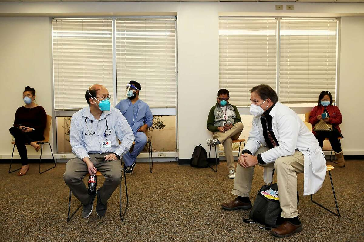 Dr. John Lai, left, and Dr. David Vaughan converse in a room with other staff members as they wait to receive a coronavirus vaccine at Seton Medical Center on Monday, December 21, 2020, in Daly City, Calif.
