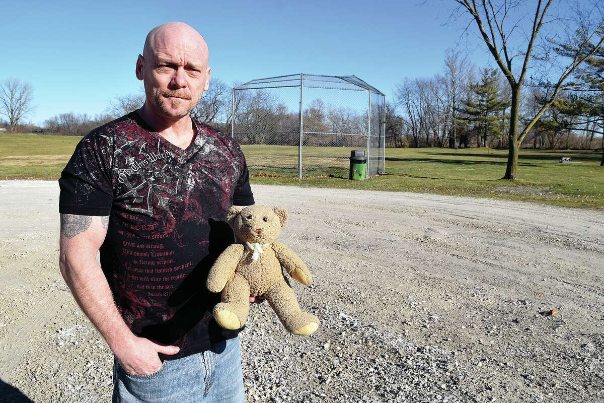 Collin DeLong holds a teddy bear containing an urn and ashes. He found the bear and is looking for the family to whom it belongs.