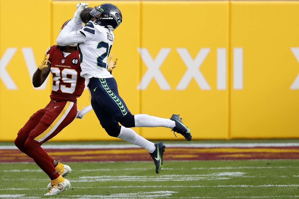 LANDOVER, MARYLAND - DECEMBER 20: Free safety D.J. Reed #29 of the Seattle Seahawks intercepts a pass intended for wide receiver Cam Sims #89 of the Washington Football Team in the second half at FedExField on December 20, 2020 in Landover, Maryland. (Photo by Tim Nwachukwu/Getty Images)