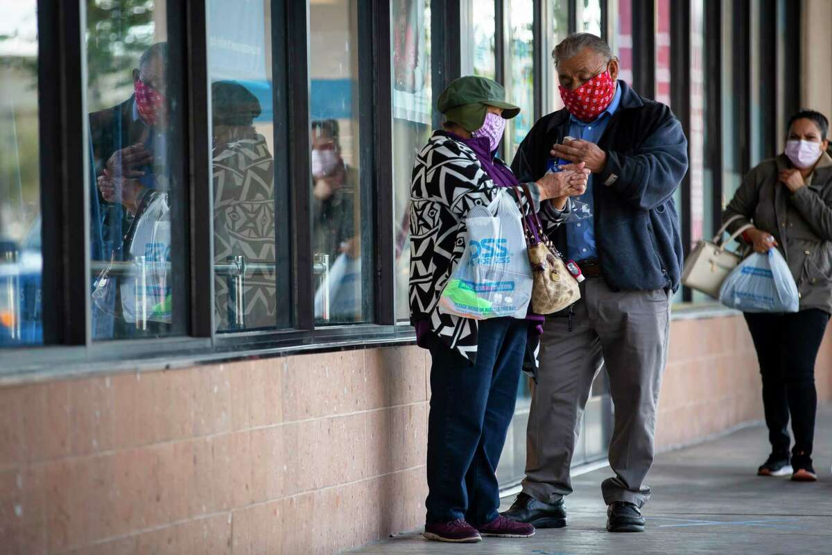 A couple sanitizes their hands after exiting the Ross store in the Gulfgate Shopping Center on Wednesday, Dec. 16, 2020.