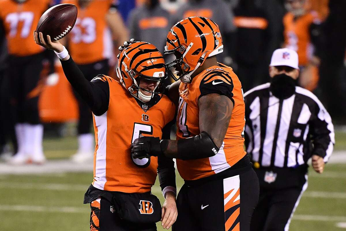 Bengals quarterback Ryan Finley (5) and tackle Fred Johnson celebrate following a first-down run during the fourth quarter.