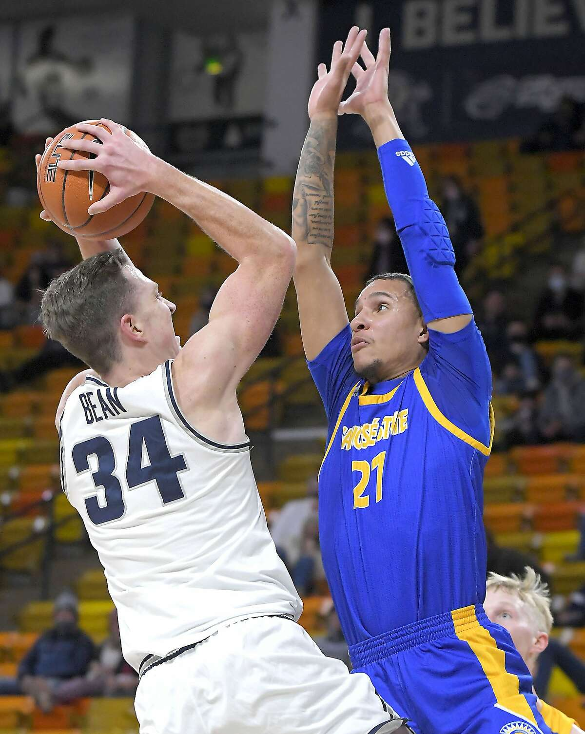 Utah State forward Justin Bean (34) shoots as San Jose State guard Kaison Hammonds (21) defends during the first half of an NCAA college basketball game Monday, Dec. 21, 2020, in Logan, Utah. (Eli Lucero/The Herald Journal via AP, Pool)