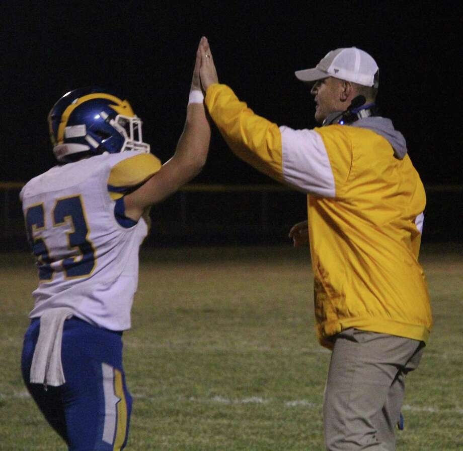 Evart offensive coordinator Ken Ranjel (right) celebrates with a player during the Wildcats playoff win over McBain. (Pioneer photo/John Raffel)