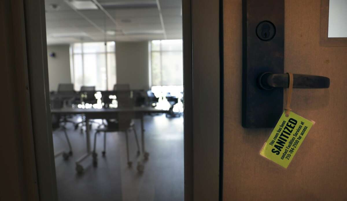 """A sign indicating """"sanitized"""" hangs on a door to a classroom."""