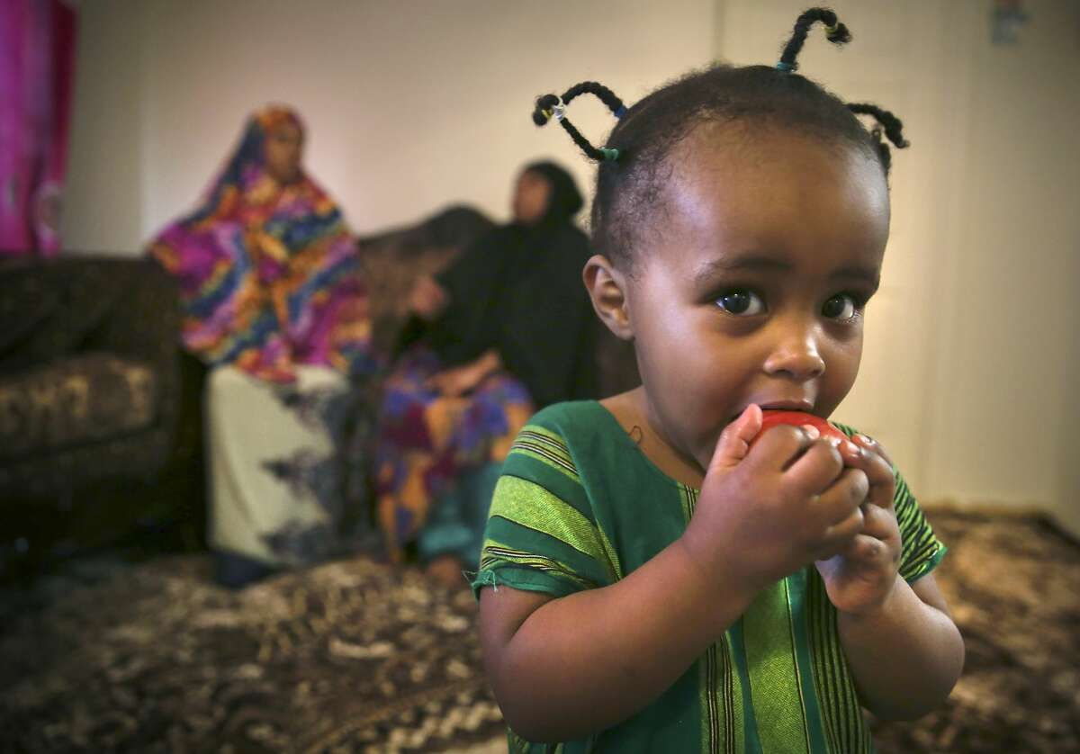 Rahma, 2 year-old daughter of Halimo Mohamed, eats an apple as her mother talks with Sabaya Chabat in Halimo?•s apartment in Amarillo, Texas, on Friday, Aug.14, 2020. Both ladies worked at Tyson in Amarillo, Sabaya had coronavirus two times and Halimo had it three times.