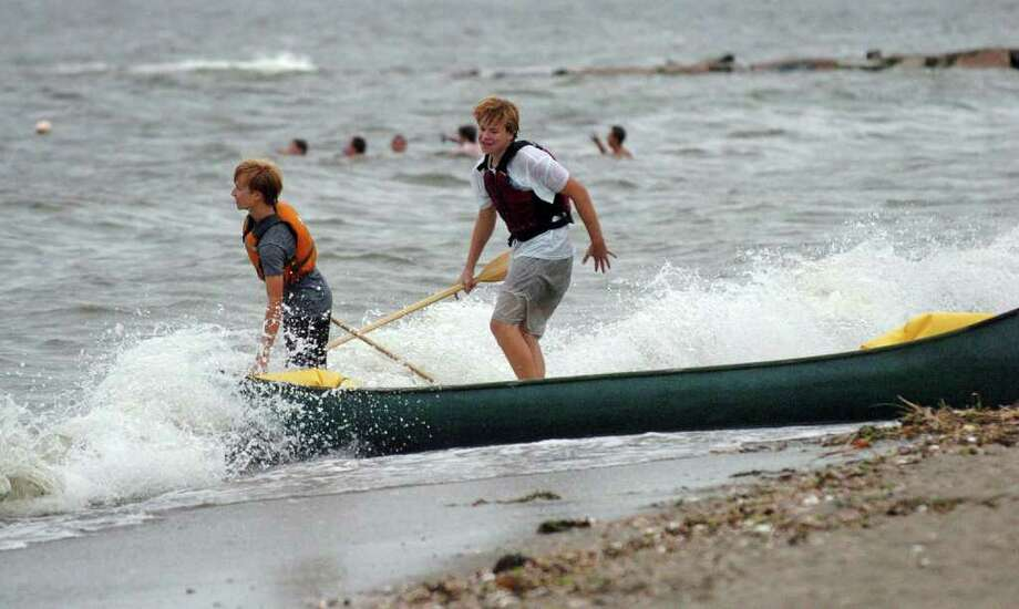 The brunt of Hurricane Earl decided not to pummel Connecticut like predicted on Friday, September 3, 2010. Penfield Beach in Fairfield, Conn., brought out many people to enjoy the water and beach even though winds and waves were high. Here, Bryce Kopp, 15, left, and his friend Charlie Wolstenholme, 16, attempt to take out a canoe in the choppy waters of the Long Island Sound. Photo: Christian Abraham / Connecticut Post