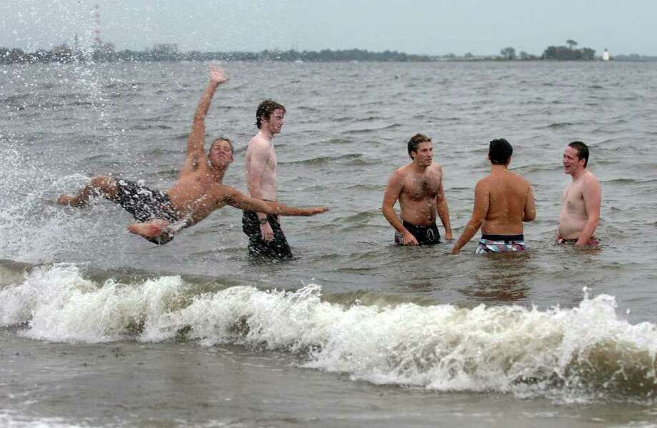 The brunt of Hurricane Earl decided not to pummel Connecticut like predicted on Friday, September 3, 2010. Penfield Beach in Fairfield, Conn., brought out many people to enjoy the water and beach even though winds and waves were high. Here, Andrew Kern, of Fairfield, left, leaps into the surf as he hangs out in the water with his buddies. Photo: Christian Abraham / Connecticut Post