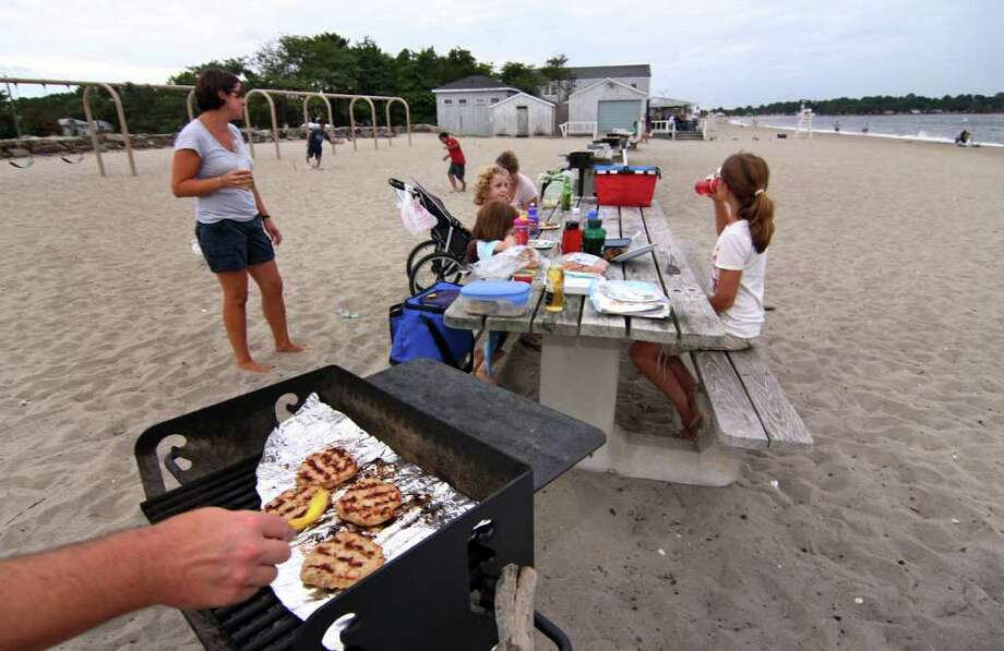 The brunt of Hurricane Earl decided not to pummel Connecticut like predicted on Friday, September 3, 2010. Penfield Beach in Fairfield, Conn., brought out many people to enjoy the water and beach even though winds and waves were high. Here, the Biadri and Alexander familes decided to have a cookout on the beach as storm clouds hover. Photo: Christian Abraham / Connecticut Post