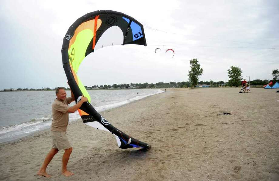 Leigh Wierzeicki helps pull a in a kite as kitesurfers on Short Beach in Stratford wait for stronger wind on Friday, September 3, 2010. Photo: Lindsay Niegelberg / Connecticut Post